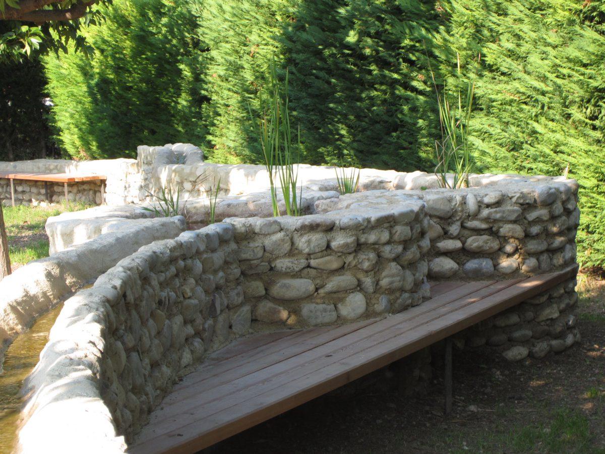 """muret en galets de rivière qui intègre des bancs """"rendez-vous"""" en mélèze"""